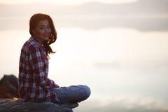 Junge Frau, die durch den See sitzt Stockbild