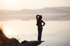 Junge Frau, die durch den See sitzt Stockfotos