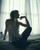 Junge Frau, die durch ein Fenster auf einem Bett sitzt Stockfoto