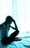 Junge Frau, die durch ein Fenster auf einem Bett sitzt Stockbild