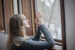 Junge Frau, die durch Fenster betet Lizenzfreie Stockbilder