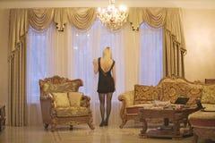 Junge Frau, die durch Fenster im Wohnzimmer schaut Stockbild