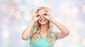 Junge Frau, die durch Fingergläser schaut Lizenzfreies Stockbild