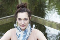Junge Frau, die durch Teich 002 sich entspannt Lizenzfreies Stockbild