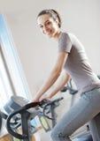 Junge Frau, die ein Übungsfahrrad reitet Stockbild