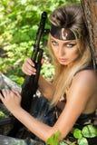 Junge Frau, die ein automatisches Sturmgewehr hält Stockbilder