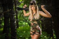 Junge Frau, die ein automatisches Sturmgewehr hält Stockfoto