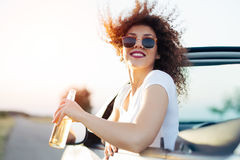 Junge Frau, die ein Bier trinkt und den Sonnenuntergang schaut Sie sitzt in einem sportiven Auto Lizenzfreie Stockfotografie