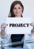 Junge Frau, die ein Blatt Papier mit dem Textprojekt hält stockfotografie