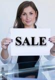 Junge Frau, die ein Blatt Papier mit dem Textverkauf hält lizenzfreies stockbild