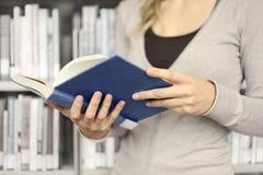 Junge Frau, die ein Buch in der Bibliothek liest Stockfotografie