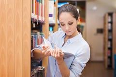 Junge Frau, die ein Buch an der Bibliothek liest Stockbild