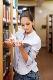 Junge Frau, die ein Buch an der Bibliothek liest Stockfotos