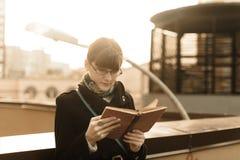 Junge Frau, die ein Buch in der Stadt liest Lizenzfreie Stockfotos