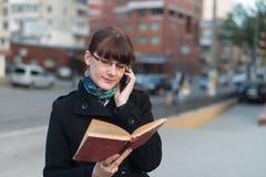 Junge Frau, die ein Buch in der Stadt liest Stockfoto