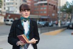 Junge Frau, die ein Buch in der Stadt liest Lizenzfreies Stockbild