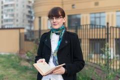 Junge Frau, die ein Buch in der Stadt liest Stockbild