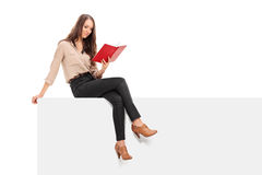 Junge Frau, die ein Buch gesetzt auf einer Platte liest Lizenzfreie Stockbilder