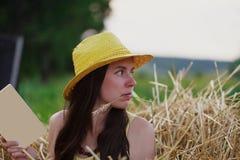 Junge Frau, die ein Buch hält und besorgt hinter schaut Lizenzfreie Stockfotografie