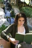 Junge Frau, die ein Buch im Herbst liest Stockfoto