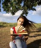 Junge Frau, die ein Buch liest Stockbild