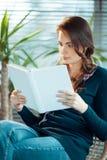 Junge Frau, die ein Buch liest Stockfoto
