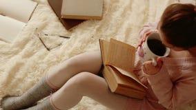 Junge Frau, die ein Buch liest und Kaffee trinkt stock footage