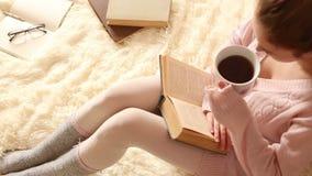 Junge Frau, die ein Buch liest und Kaffee trinkt stock video footage