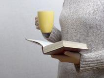 Junge Frau, die ein Buch liest und Tasse Tee oder Kaffee hält Getontes Bild Stockfotografie