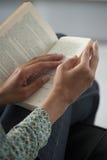 Junge Frau, die ein Buch, Nahaufnahme, auf Haupt- Innen-backgroun liest Lizenzfreie Stockfotos