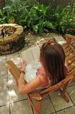 Junge Frau, die ein Buch sich entspannt und liest Stockfotografie