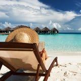Junge Frau, die ein Buch am Strand liest Lizenzfreie Stockfotos