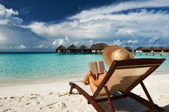 Junge Frau, die ein Buch am Strand liest Lizenzfreie Stockbilder