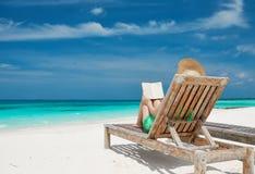 Junge Frau, die ein Buch am Strand liest Stockbild