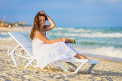 Junge Frau, die ein Buch am Strand liest Stockfotos