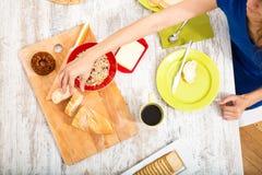 Junge Frau, die ein europäisches Frühstück zubereitet Lizenzfreie Stockfotografie