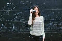 Junge Frau, die ein Foto mit einer alten Kamera macht Stockfoto