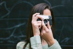 Junge Frau, die ein Foto mit einer alten Kamera macht Stockfotos