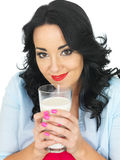 Junge Frau, die ein frisches Glas Milch mit beiden Händen hält Stockbilder