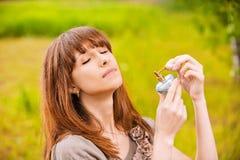 Junge Frau, die ein Geruch setzt Stockfotografie