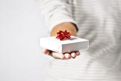 Junge Frau, die ein Geschenk anbietet Lizenzfreies Stockbild