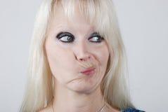 Junge Frau, die ein Gesicht bildet Stockbilder