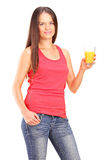 Junge Frau, die ein Glas Orangensaft hält Lizenzfreies Stockfoto