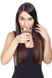 Junge Frau, die ein Glas Wasser trinkt stockfotos
