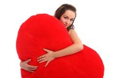 Junge Frau, die ein großes rotes Inneres anhält Stockbilder