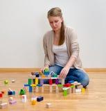 Junge Frau, die ein Haus aufbaut Stockfoto