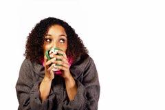 Junge Frau, die ein heißes Getränk umarmt Stockbilder