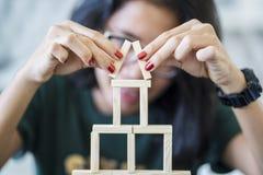 Junge Frau, die ein Holzklotzhaus macht stockbild