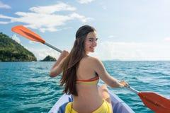 Junge Frau, die ein Kanu auf dem Meer während der Sommerferien schaufelt Stockfotos