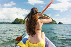 Junge Frau, die ein Kanu auf dem Meer während der Sommerferien schaufelt Stockbilder